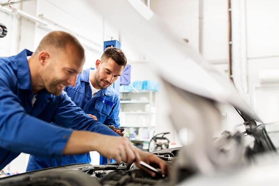 Bilverksted Jessheim - mekanikere arbeider med motor på en bil