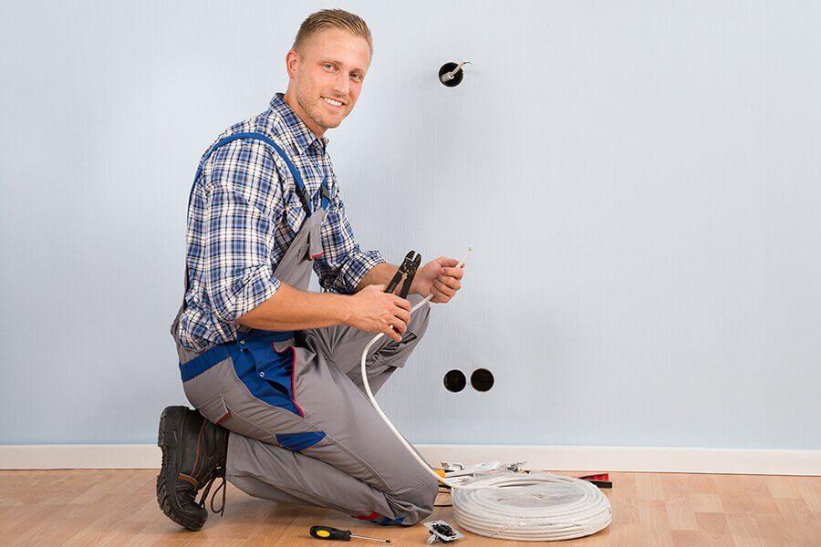 Elektriker Jessheim - elektriker som arbeider med en kabel for montering av TV